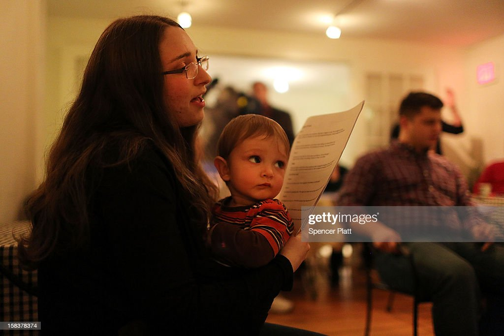 Alexandra Kulick and her 9-month-old son Frank John attend a prayer service at a local coffee shop after the shooting at the nearby Sandy Hook School on December 14, 2012 in Newtown, Connecticut. Twenty-seven people are dead, including 20 children, after a gunman identified as Adam Lanza in news reports, opened fire in the school. Lanza also reportedly died at the scene.