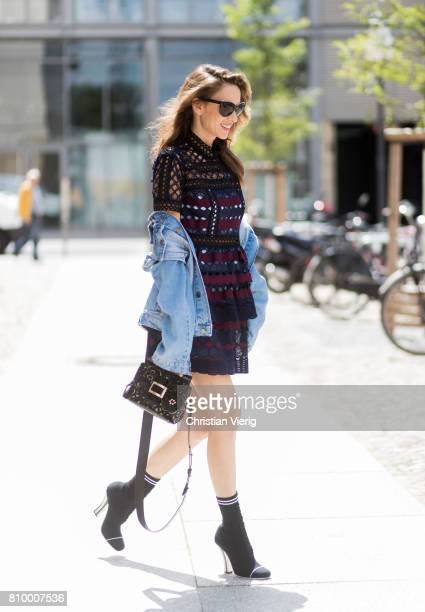 Alexandra Lapp wearing a mini lace dress in navy blue and heady red from SelfPortrait a Roger Viv mini bag crafted in suede with waterjet cut Guipure...