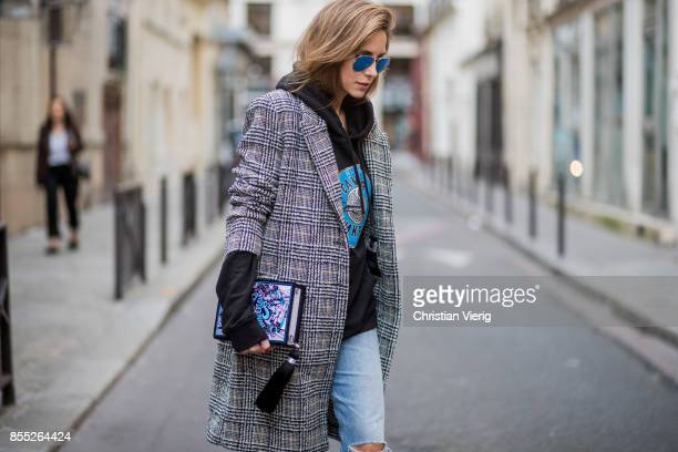Alexandra Lapp wearing a selfmade hoodie in black with a handpainted Russian Caviar motif from Wodka Ogurez a book clutch with 'Alice adventures in...