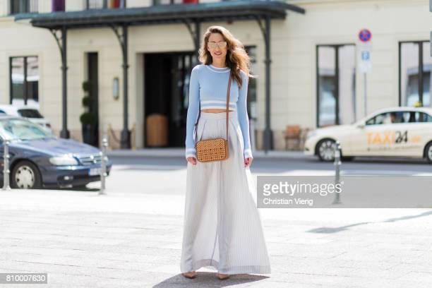 Alexandra Lapp wearing bluewhite striped wide leg pants from Zimmermann a baby blue cropped top from HM gold mirrored cateye sunglasses from Karl by...