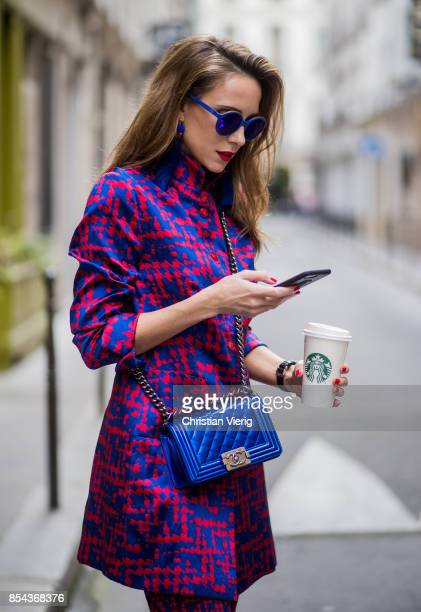 Alexandra Lapp with phone and Starbucks coffee to go wearing a twopiece in red and blue by Riani a blue lacquer Chanel Boy bag blue sunglasses by...
