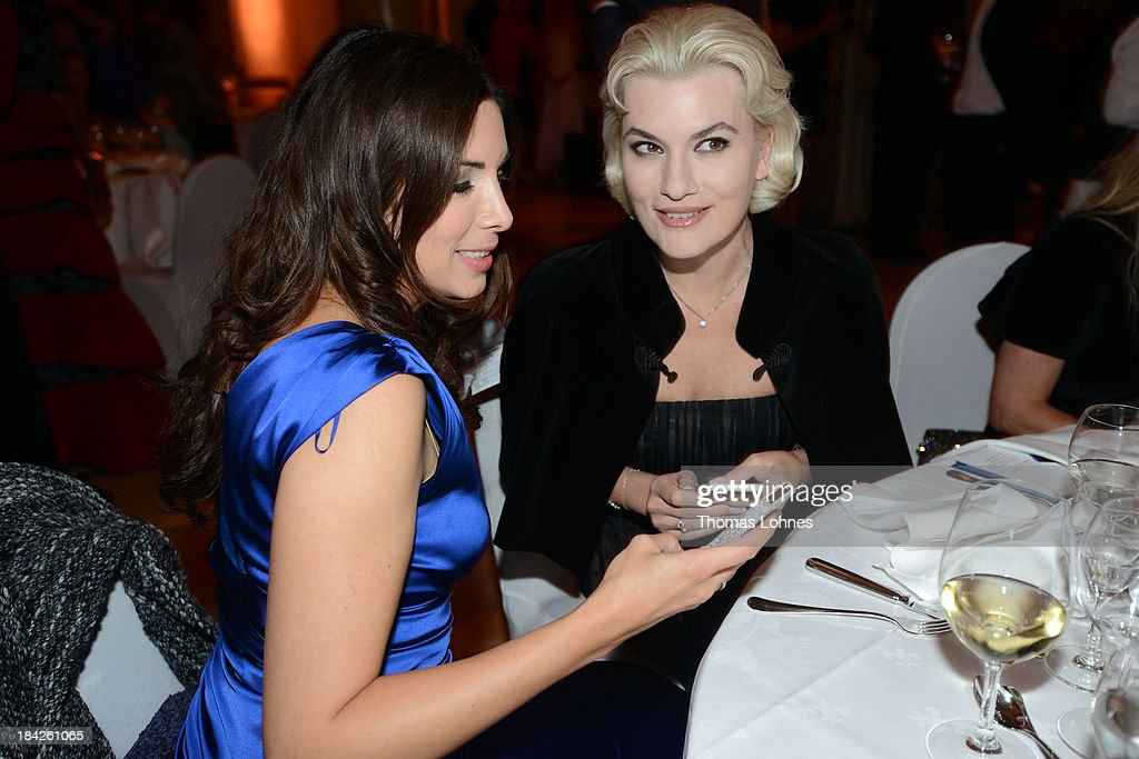 Alexandra Polzin (l) and Kriemhild Siegel (r) look to there smartphones during the Minx fashion night at Residenz on October 12, 2013 in Wuerzburg, Germany. The benefit of the charity gala is for the aid organisation 'Sauti Kuu' of Auma Obama. Behind the fashion label Minx stands Eva Lutz.