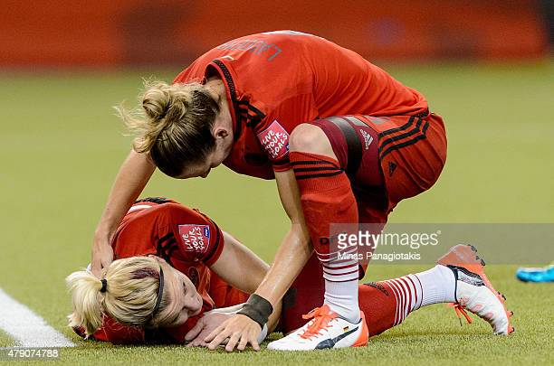 Alexandra Popp of Germany suffers a head injury as she is checked on by Simone Laudehr in the first half against the United States in the FIFA...