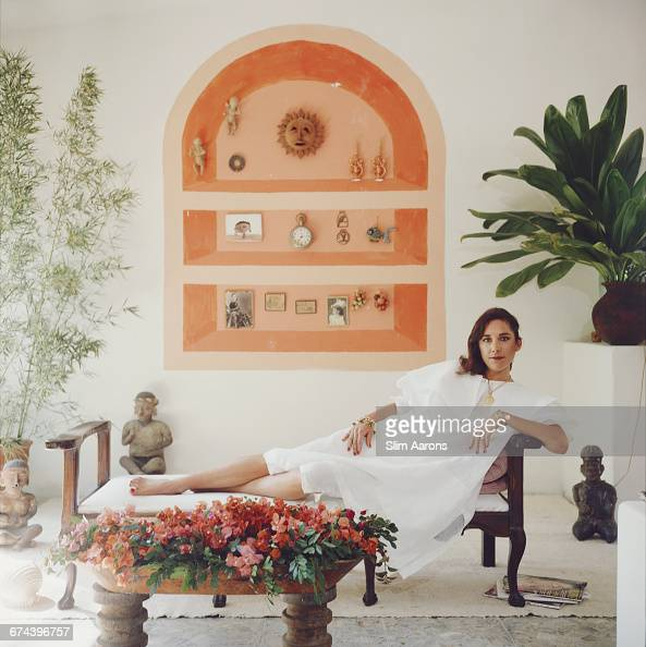 Alexandra Redo reclining among Mayan statues and tropical plants on the porch of the Redo family owned plantation 'Eldorado' in the Culiacán Valley...