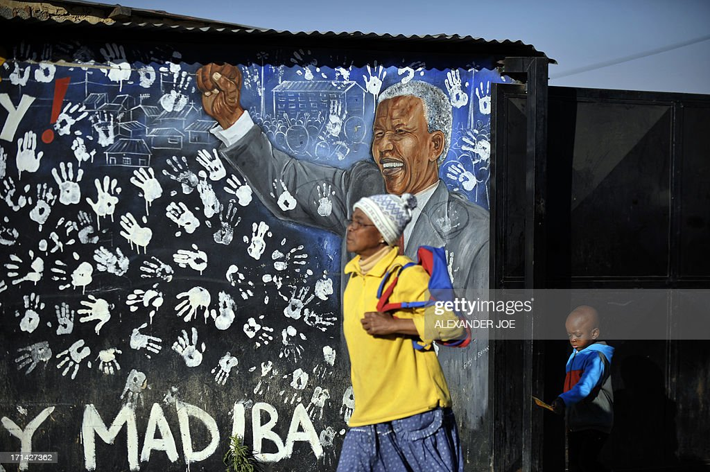 Alexandra's residents walk past a painting of anti-apartheid icon Nelson Mandela, on June 24, 2013 in Alexandra near Johannesburg. A statement issued by the South African government reported that former South African president Nelson Mandela's health was in a critical stage after his condition in hospital worsened over the course of 24 hours.
