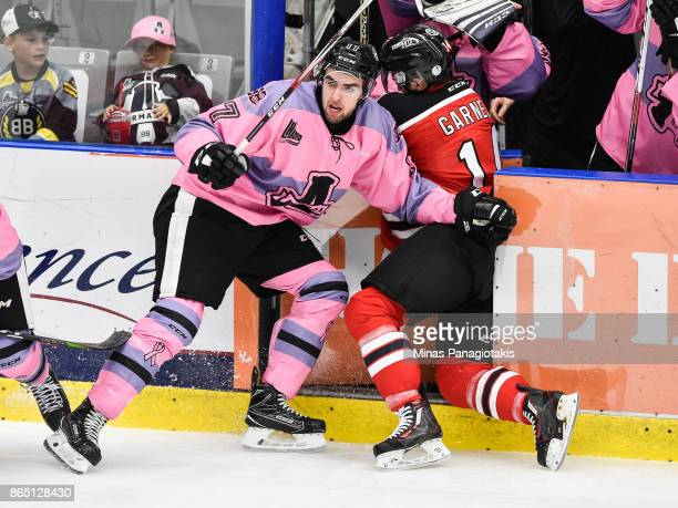 Alexandre Alain of the BlainvilleBoisbriand Armada checks Olivier Garneau of the Quebec Remparts through the door during the QMJHL game at Centre...