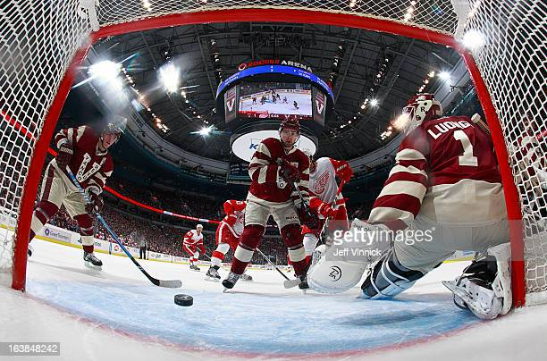 Alexandre Burrows Dan Hamhuis and Roberto Luongo of the Vancouver Canucks watch a shot by Henrik Zetterberg of the Detroit Red Wings enter the net...