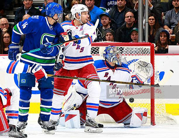 Alexandre Burrows of the Vancouver Canucks and Dan Girardi of the New York Rangers watch a shot by Alexander Edler of the Vancouver Canucks beat...