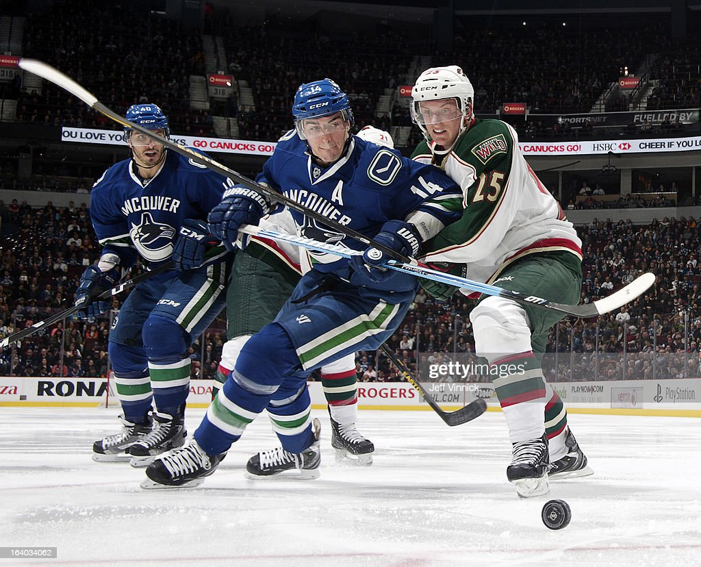 Alexandre Burrows #14 of the Vancouver Canucks and Dany Heatley #15 of the Minnesota Wild battle for the puck during their NHL game at Rogers Arena March 18, 2013 in Vancouver, British Columbia, Canada.