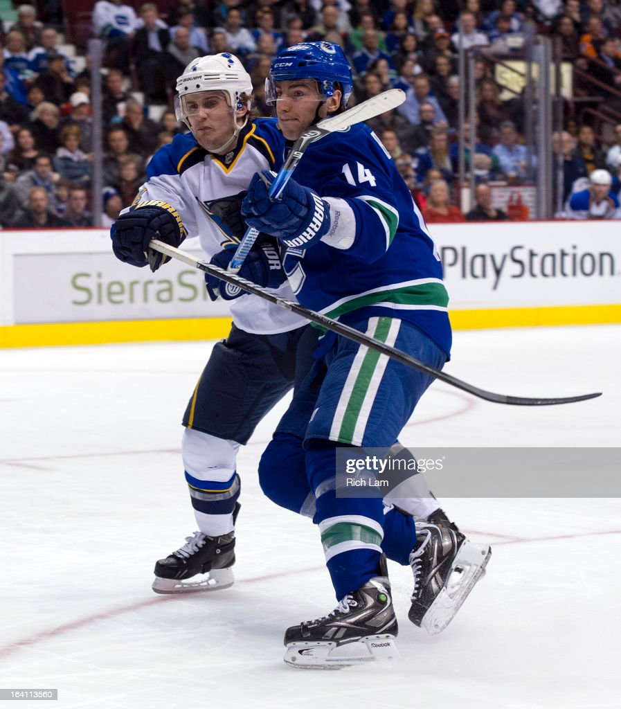 Alexandre Burrows #14 of the Vancouver Canucks and Kris Russell #4 of the St. Louis Blues battle for position while chasing a loose puck in the corner during the third period in NHL action on March 19, 2013 at Rogers Arena in Vancouver, British Columbia, Canada.