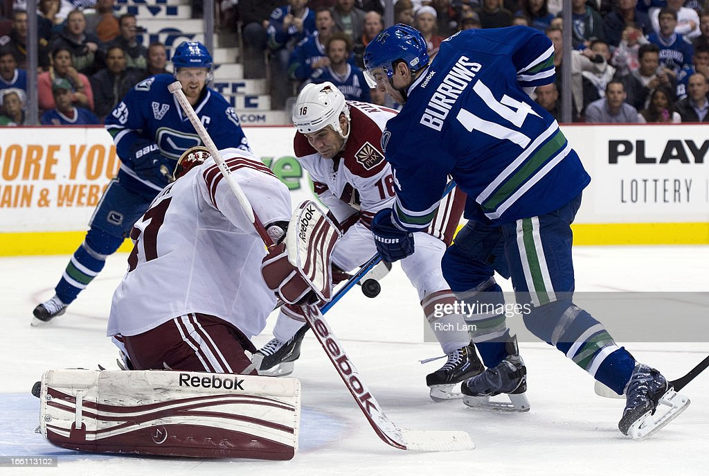 Alexandre Burrows #14 of the Vancouver Canucks battles with Rostislav Klesla #16 of the Phoenix Coyotes for the loose puck after goalie Mike Smith #41 of the Phoenix Coyotes made a save during the third period in NHL action on April 08, 2013 at Rogers Arena in Vancouver, British Columbia, Canada. Henrik Sedin #33 of the Vancouver Canucks is seen in the background.