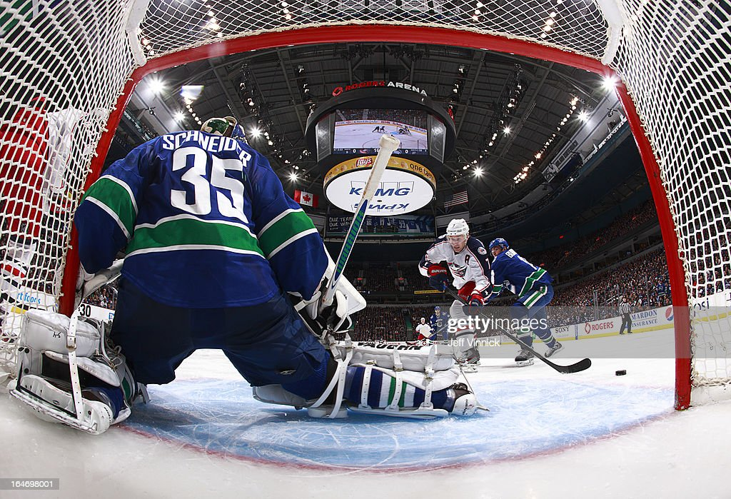 <a gi-track='captionPersonalityLinkClicked' href=/galleries/search?phrase=Alexandre+Burrows&family=editorial&specificpeople=592489 ng-click='$event.stopPropagation()'>Alexandre Burrows</a> #14 of the Vancouver Canucks checks Jack Johnson #7 of the Columbus Blue Jackets while <a gi-track='captionPersonalityLinkClicked' href=/galleries/search?phrase=Cory+Schneider&family=editorial&specificpeople=696908 ng-click='$event.stopPropagation()'>Cory Schneider</a> #35 of the Canucks makes a save during their NHL game at Rogers Arena March 26, 2013 in Vancouver, British Columbia, Canada. Vancouver won 1-0.