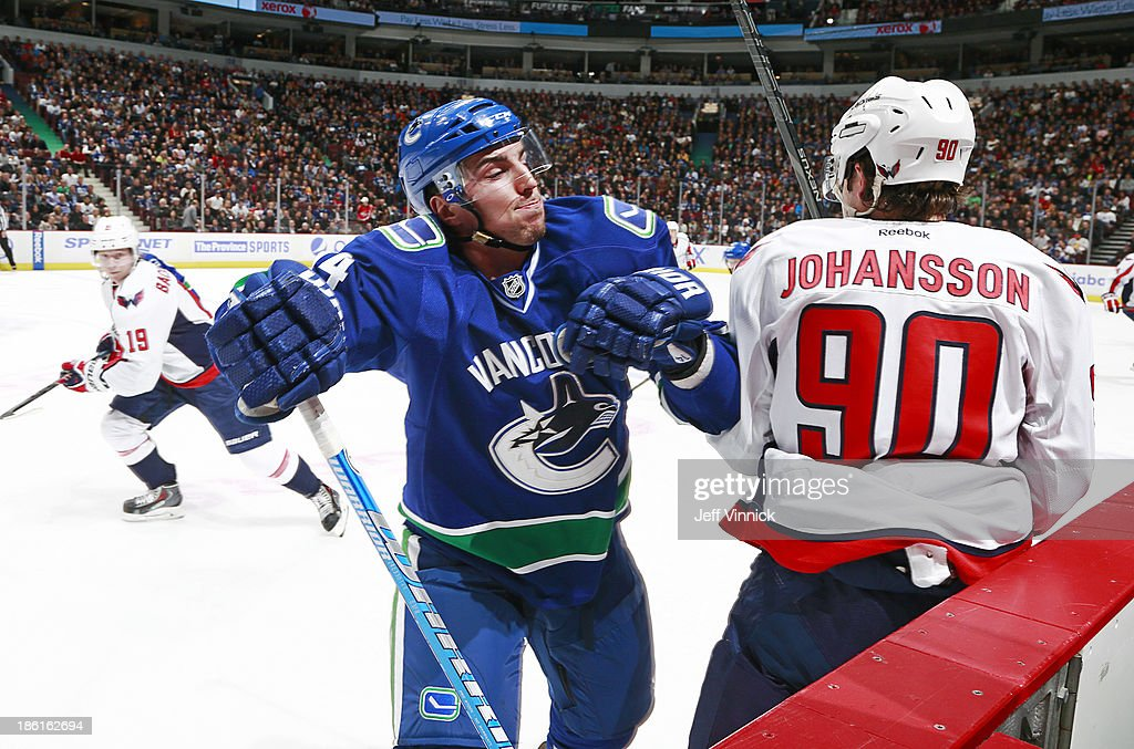 Alexandre Burrows #14 of the Vancouver Canucks checks Marcus Johansson #90 of the Washington Capitals during their NHL game at Rogers Arena on October 28, 2013 in Vancouver, British Columbia, Canada.