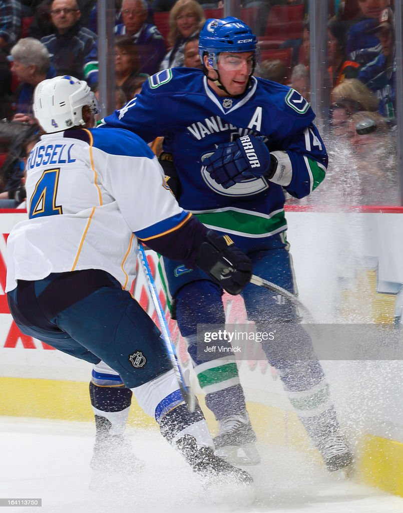 <a gi-track='captionPersonalityLinkClicked' href=/galleries/search?phrase=Alexandre+Burrows&family=editorial&specificpeople=592489 ng-click='$event.stopPropagation()'>Alexandre Burrows</a> #14 of the Vancouver Canucks eyes the puck while being checked by <a gi-track='captionPersonalityLinkClicked' href=/galleries/search?phrase=Kris+Russell&family=editorial&specificpeople=879805 ng-click='$event.stopPropagation()'>Kris Russell</a> #4 of the St. Louis Blues during their NHL game at Rogers Arena March 19, 2013 in Vancouver, British Columbia, Canada. Vancouver won 3-2.