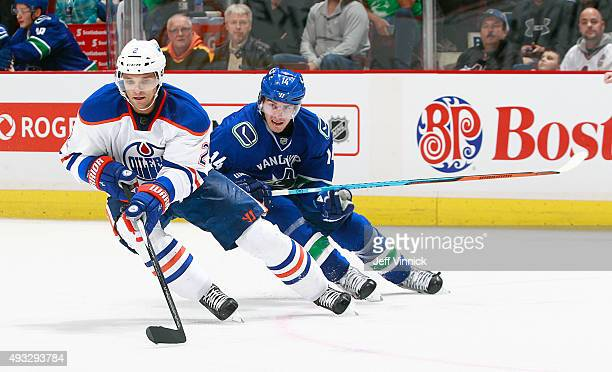 Alexandre Burrows of the Vancouver Canucks pursues Andrej Sekera of the Edmonton Oilers during their NHL game at Rogers Arena October 18 2015 in...