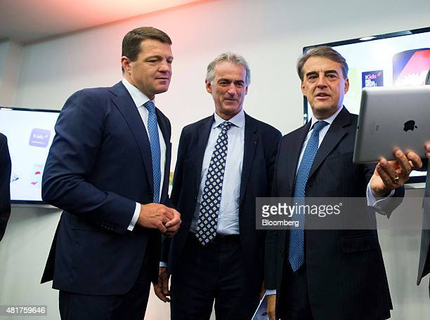 Alexandre de Juniac chief executive officer of Air FranceKLM Group right holds an Apple Inc iPad as he stands with Frederic Gagey chief executive...