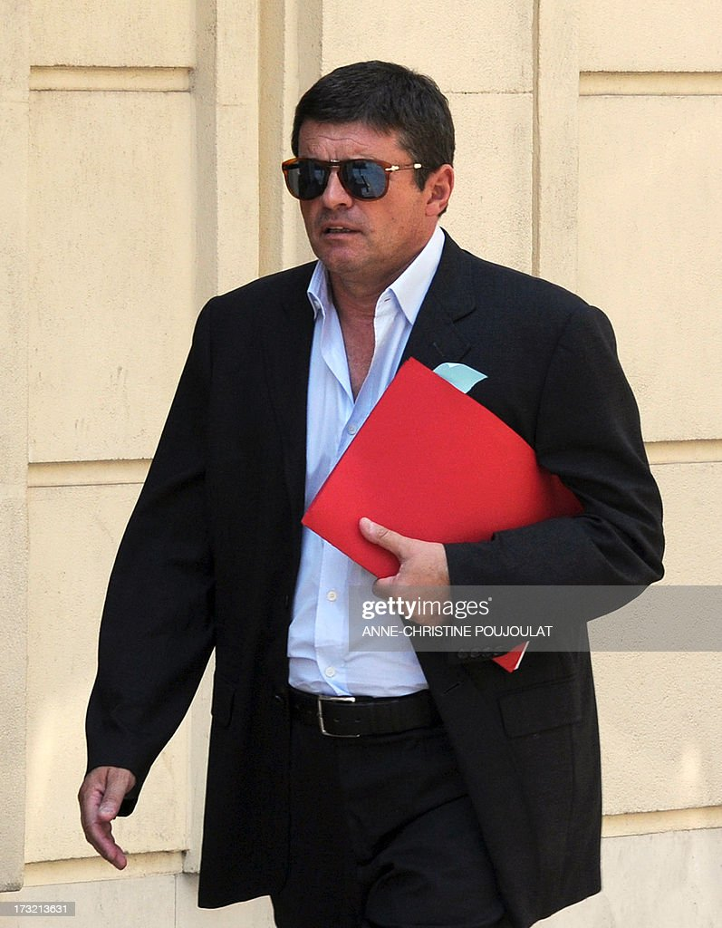 Alexandre Guerini, an entrepreneur specialized in waste management and brother of the president of the General Council of the Bouches-du-Rhone, holds documents as he arrives on July 10, 2013 at the courthouse in Marseille, southern France, to be heard by a judge as part of an inquiry into alleged fraudulent public contracts.