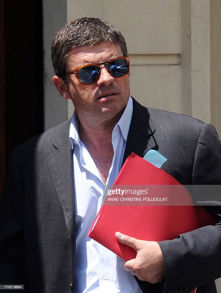 Alexandre Guerini, an entrepreneur specialized in waste management and brother of the president of the General Council of the Bouches-du-Rhone, holds documents as he arrives on July 10, 2013 at the courthouse in Marseille, southern France, to be heard by a judge as part of an inquiry into alleged fraudulent public contracts. AFP PHOTO / ANNE-CHRISTINE POUJOULAT
