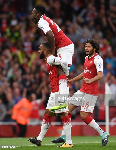 Alexandre Lacazette celebrates scoring a goal for Arsenal with Mohamed Elneny and Danny Welbeck during the Premier League match between Arsenal and...