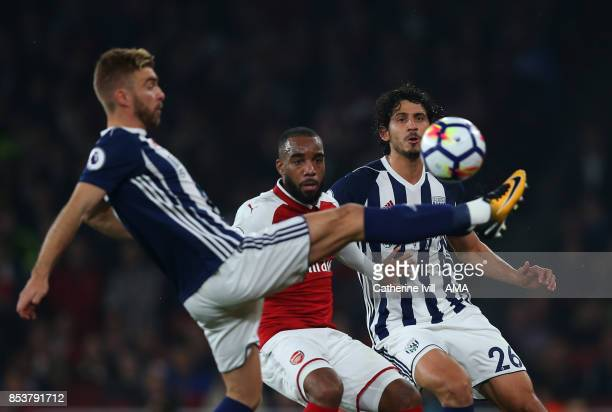 Alexandre Lacazette of Arsenal and Ahmed Hegazy of West Bromwich Albion watch as James Morrison of West Bromwich Albion clears the ball during the...