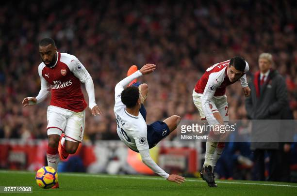 Alexandre Lacazette of Arsenal and Dele Alli of Tottenham Hotspur in action during the Premier League match between Arsenal and Tottenham Hotspur at...