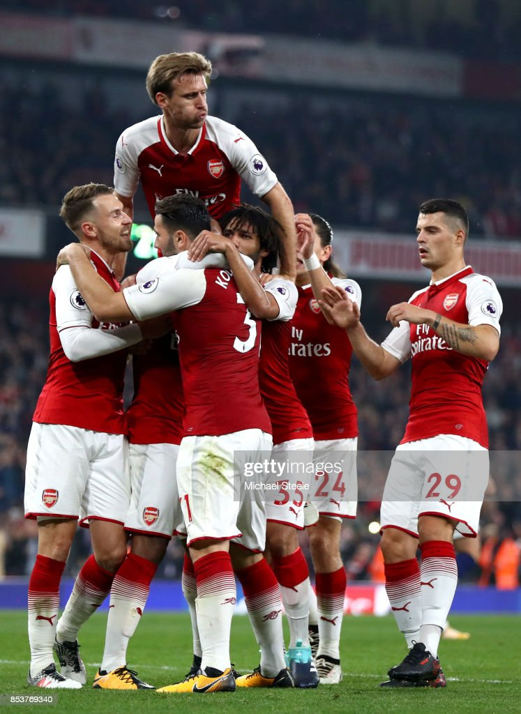 Alexandre Lacazette of Arsenal (obscured) celebrates with team mates as he scores their second goal from a penalty during the Premier League match between Arsenal and West Bromwich Albion at Emirates Stadium on September 25, 2017 in London, England.