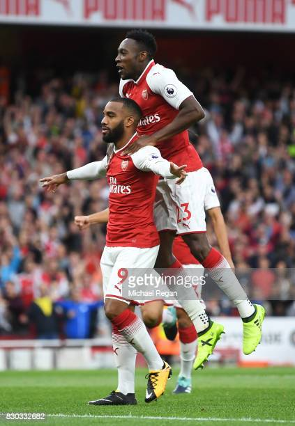 Alexandre Lacazette of Arsenal celebrates with teammate Danny Welbeck after scoring the opening goal during the Premier League match between Arsenal...
