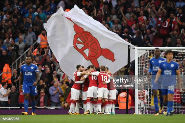 Alexandre Lacazette of Arsenal celebrates with teammates after scoring the opening goal during the Premier League match between Arsenal and Leicester...