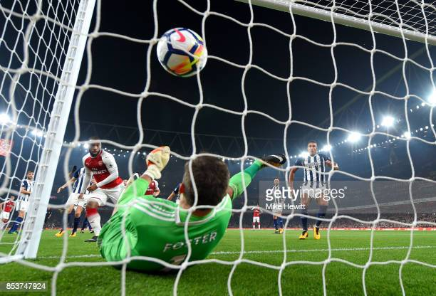 Alexandre Lacazette of Arsenal heads past Ben Foster of West Bromwich Albion as he scores their first goal during the Premier League match between...