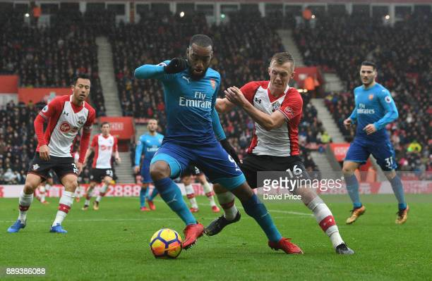 Alexandre Lacazette of Arsenal is challenged by James WardProwse of Southampton during the Premier League match between Southampton and Arsenal at St...