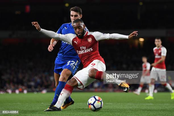 Alexandre Lacazette of Arsenal is challenged by Matty James of Leicester City during the Premier League match between Arsenal and Leicester City at...