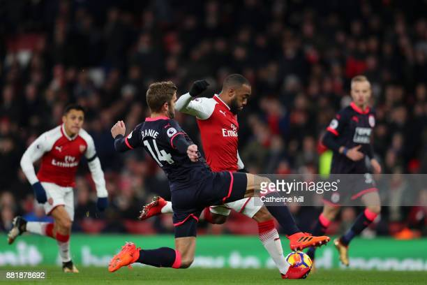 Alexandre Lacazette of Arsenal scores his sides first goal past Martin Cranie of Huddersfield Town during the Premier League match between Arsenal...