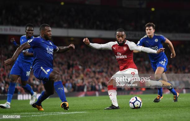 Alexandre Lacazette of Arsenal shoots on goal as Wes Morgan of Leicester City closes in during the Premier League match between Arsenal and Leicester...