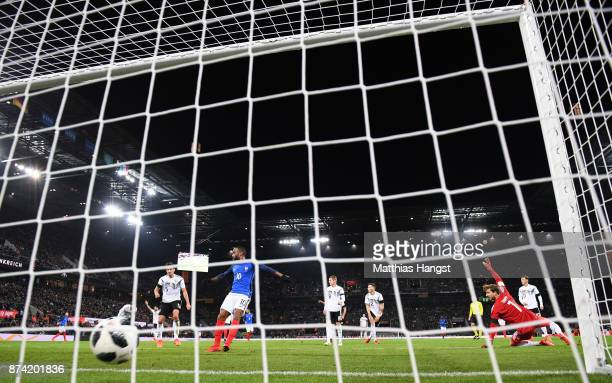Alexandre Lacazette of France scores his sides first goal past Kevin Trapp of Germany during the international friendly match between Germany and...