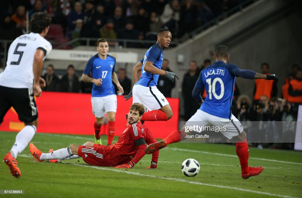 Alexandre Lacazette of France (10) scores the first goal for France with an assist from Anthony Martial (center) while goalkeeper of Germany Kevin Trapp looks on during the international friendly match between Germany and France at RheinEnergieStadion on November 14, 2017 in Cologne, Germany.