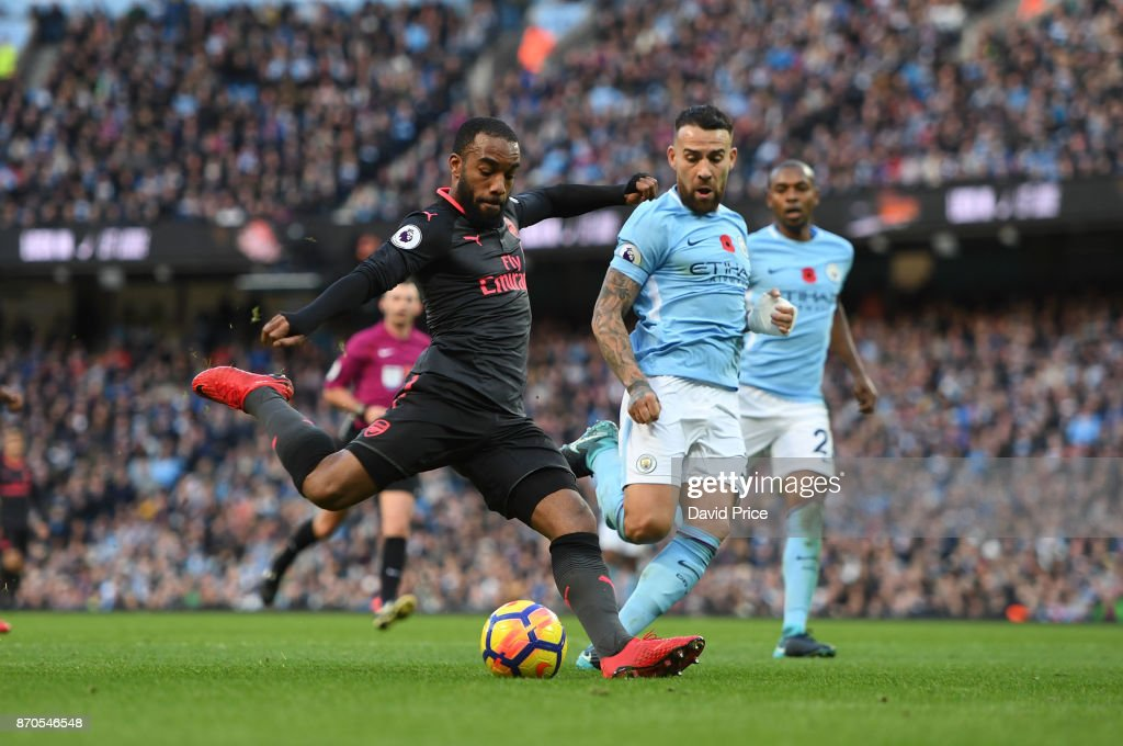 Alexandre Lacazette scores a goal for Arsenal under pressure from Nicolas Otamendi of Man City during the Premier League match between Manchester City and Arsenal at Etihad Stadium on November 5, 2017 in Manchester, England.