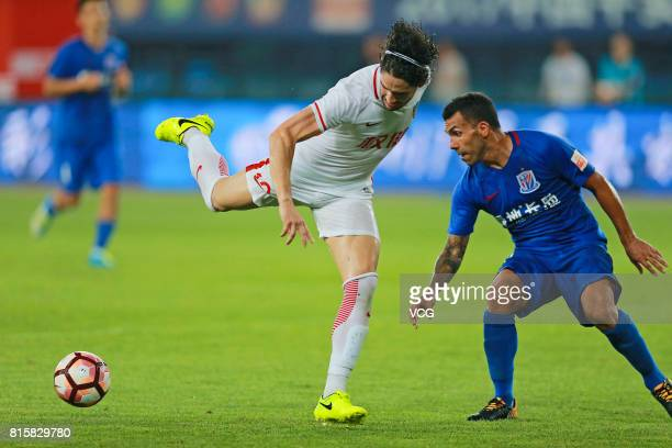 Alexandre Pato of Tianjin Quanjian and Carlos Tevez of Shanghai Shenhua compete for the ball during the 17th round match of 2017 Chinese Football...