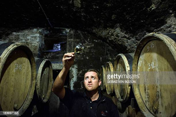 Alexandre Vandelle owner of the Chateau l'Etoile vineyard checks the colour of a glass of wine in the cellar of his vineyard on October 8 2013 in...