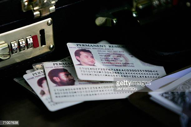Permanent residence cards known as green cards rest on the checkin table as resident aliens arrive for a naturalization ceremony at George...