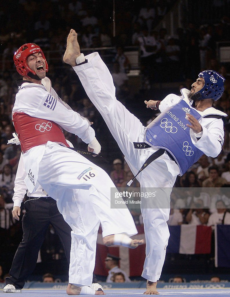 Alexandros Nikolaidis of Greece (red) avoids a kick from Ibrahim Kamal of Jordan in the men's over 80 kg Taekwondo repechage match on August 29, 2004 during the Athens 2004 Summer Olympic Games at the Sports Pavilion part of the Faliro Coastal Zone Olympic Complex.