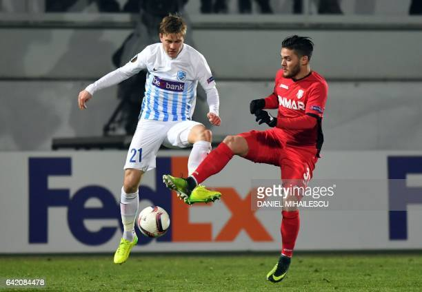 Alexandru Ionita of Astra Giurgiu vies for the ball with Jere Uronen of KRC Genk during the UEFA Europa League round of 32 firstleg football match...