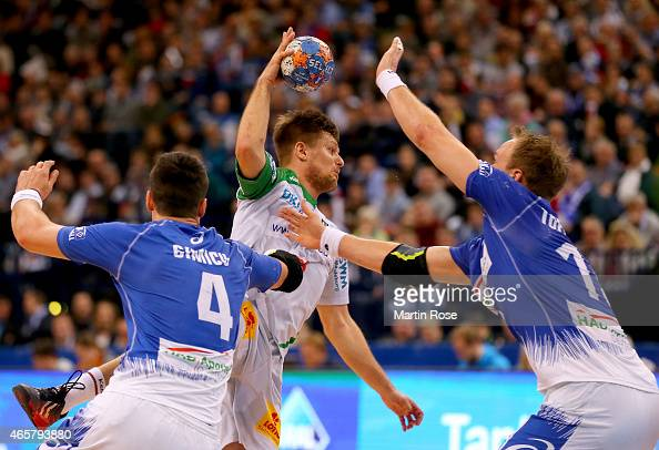 Alexandru Simicu and Henrik Toft Hansen of Hamburg challenges Bartosz Jurecki of Magdeburg during the DKB Bundesliga handball match between HSV...