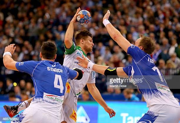 Alexandru Simicu and Henrik Toft Hansen of Hamburg challenges Bartosz Jurecki of Magdeburg during the DKB Bundesliga handball match between HSV...