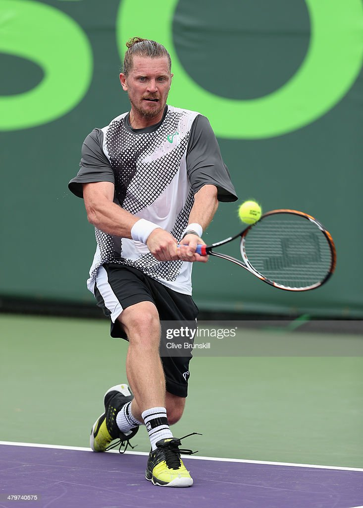Alex-Bogomolov-Jr of Russia plays a backhand against Stephane Robert of France during their first round match during day 4 at the Sony Open at Crandon Park Tennis Center on March 20, 2014 in Key Biscayne, Florida.