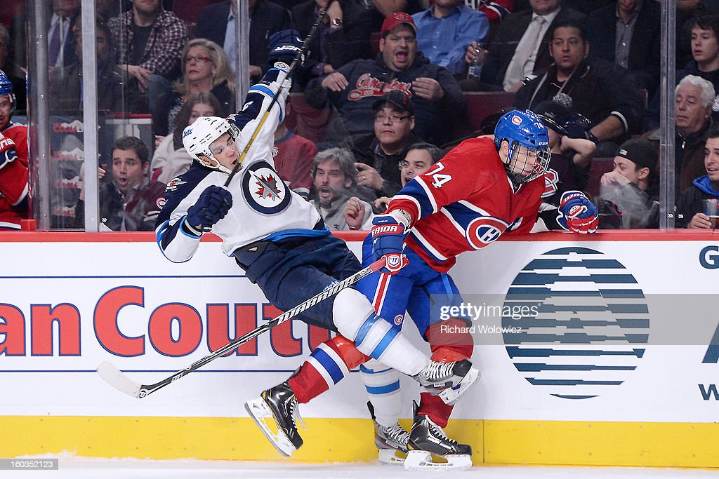<a gi-track='captionPersonalityLinkClicked' href=/galleries/search?phrase=Alexei+Emelin&family=editorial&specificpeople=723573 ng-click='$event.stopPropagation()'>Alexei Emelin</a> #74 of the Montreal Canadiens body checks <a gi-track='captionPersonalityLinkClicked' href=/galleries/search?phrase=Evander+Kane&family=editorial&specificpeople=4303789 ng-click='$event.stopPropagation()'>Evander Kane</a> #9 of the Winnipeg Jets during the NHL game at the Bell Centre on January 29, 2013 in Montreal, Quebec, Canada. The Canadiens defeated the Jets 4-3.