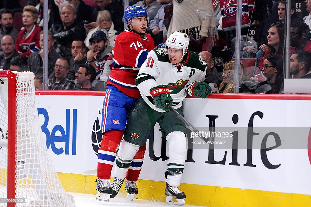 <a gi-track='captionPersonalityLinkClicked' href=/galleries/search?phrase=Alexei+Emelin&family=editorial&specificpeople=723573 ng-click='$event.stopPropagation()'>Alexei Emelin</a> #74 of the Montreal Canadiens body checks <a gi-track='captionPersonalityLinkClicked' href=/galleries/search?phrase=Zach+Parise&family=editorial&specificpeople=213606 ng-click='$event.stopPropagation()'>Zach Parise</a> #11 of the Minnesota Wild during the NHL game at the Bell Centre on November 19, 2013 in Montreal, Quebec, Canada. The Canadiens defeated the Wild 6-2.