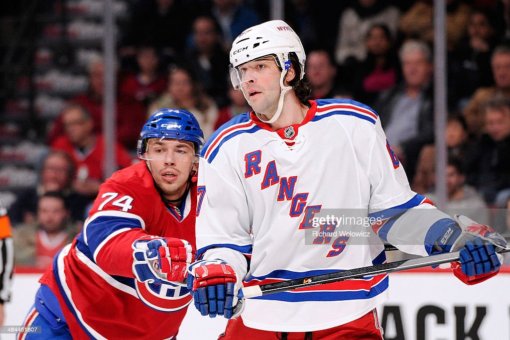 Alexei Emelin #74 of the Montreal Canadiens defends against Benoit Pouliot #67 of the New York Rangers during the NHL game at the Bell Centre on April 12, 2014 in Montreal, Quebec, Canada.