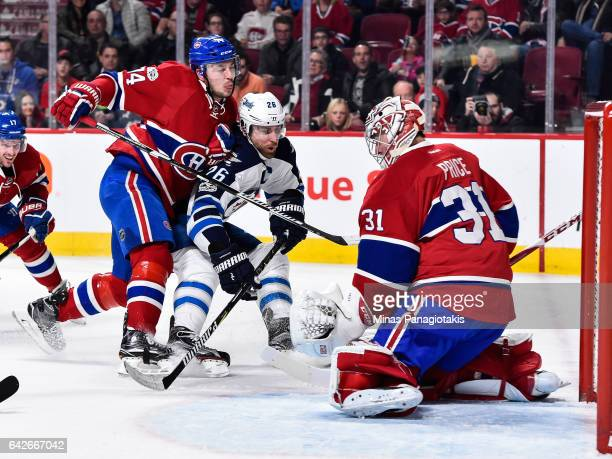 Alexei Emelin of the Montreal Canadiens defends against Blake Wheeler of the Winnipeg Jets while goaltender Carey Price makes a save during the NHL...