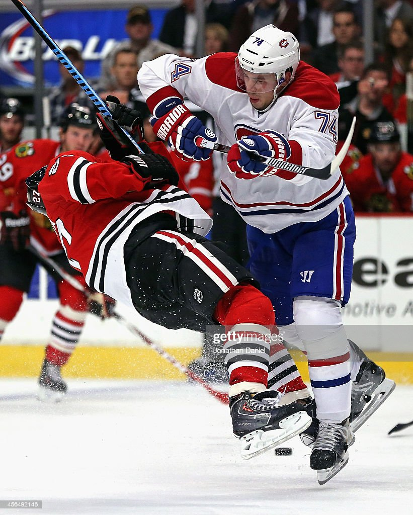 <a gi-track='captionPersonalityLinkClicked' href=/galleries/search?phrase=Alexei+Emelin&family=editorial&specificpeople=723573 ng-click='$event.stopPropagation()'>Alexei Emelin</a> #74 of the Montreal Canadiens hits <a gi-track='captionPersonalityLinkClicked' href=/galleries/search?phrase=Johnny+Oduya&family=editorial&specificpeople=3944055 ng-click='$event.stopPropagation()'>Johnny Oduya</a> #27 of the Chicago Blackhawks during a preason game at the United Center on October 1, 2014 in Chicago, Illinois.