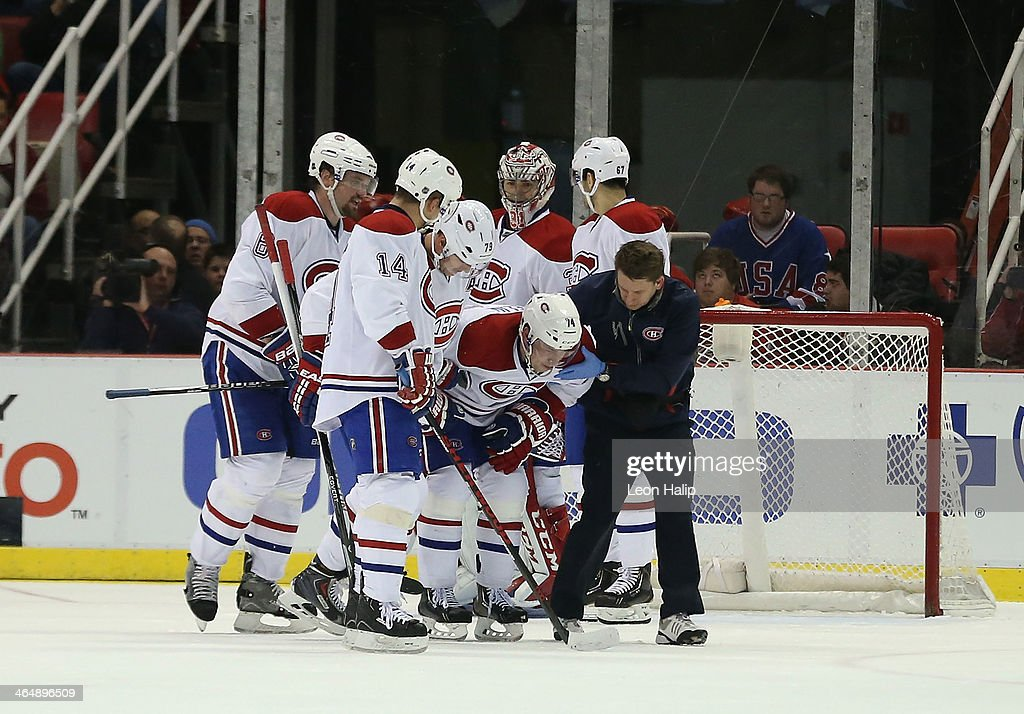 <a gi-track='captionPersonalityLinkClicked' href=/galleries/search?phrase=Alexei+Emelin&family=editorial&specificpeople=723573 ng-click='$event.stopPropagation()'>Alexei Emelin</a> #74 of the Montreal Canadiens is helped off the ice by his teammates during the third period of the game against the Detroit Red Wings at Joe Louis Arena on January 24, 2014 in Detroit, Michigan. The Wings defeated the Canadiens 4-1.